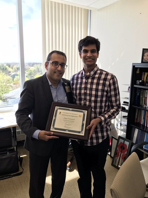 Dr. Chopra presents a certificate of completion to U of M student Aditya Yelamanchi. April 25, 2017.